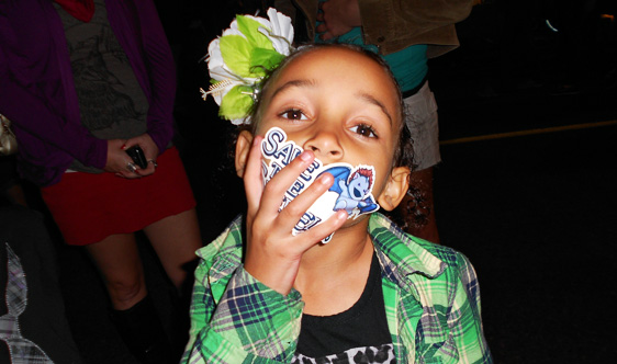 A new fan 'vocalizes' her support for the sperels by slapping one of their stickers right onto her mouth!