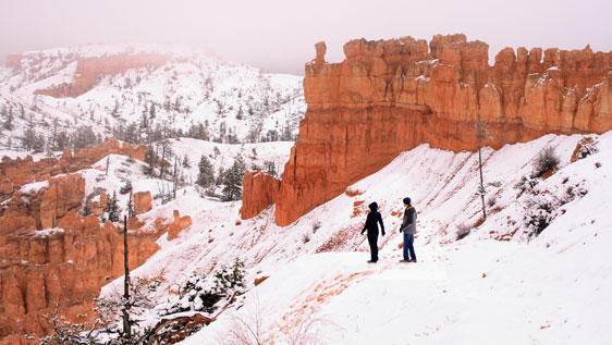 Hiking into Bryce Canyon on the snow-covered trail of Peek-A-Boo Loop